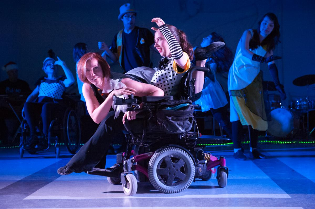 Renata Soutter is perched on top of Moni Hoffman's lap. Renata is looking into the camera smiling and Moni has her arms up in the air laughing. They are dancing under a textured blue light.
