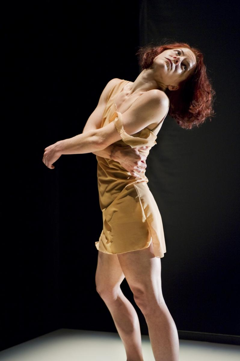 "Sonsherée Giles, throwing her head back, wearing a tan colored dress, which was a costume in the production of ""HyperReal."""