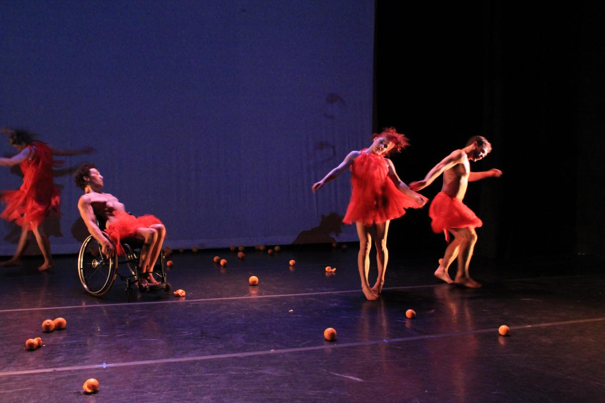 Oranges litter the stage. Four dancers in bright red costumes in synchronized motion; swirling, delirious, in an intoxicated state, moving across the stage.
