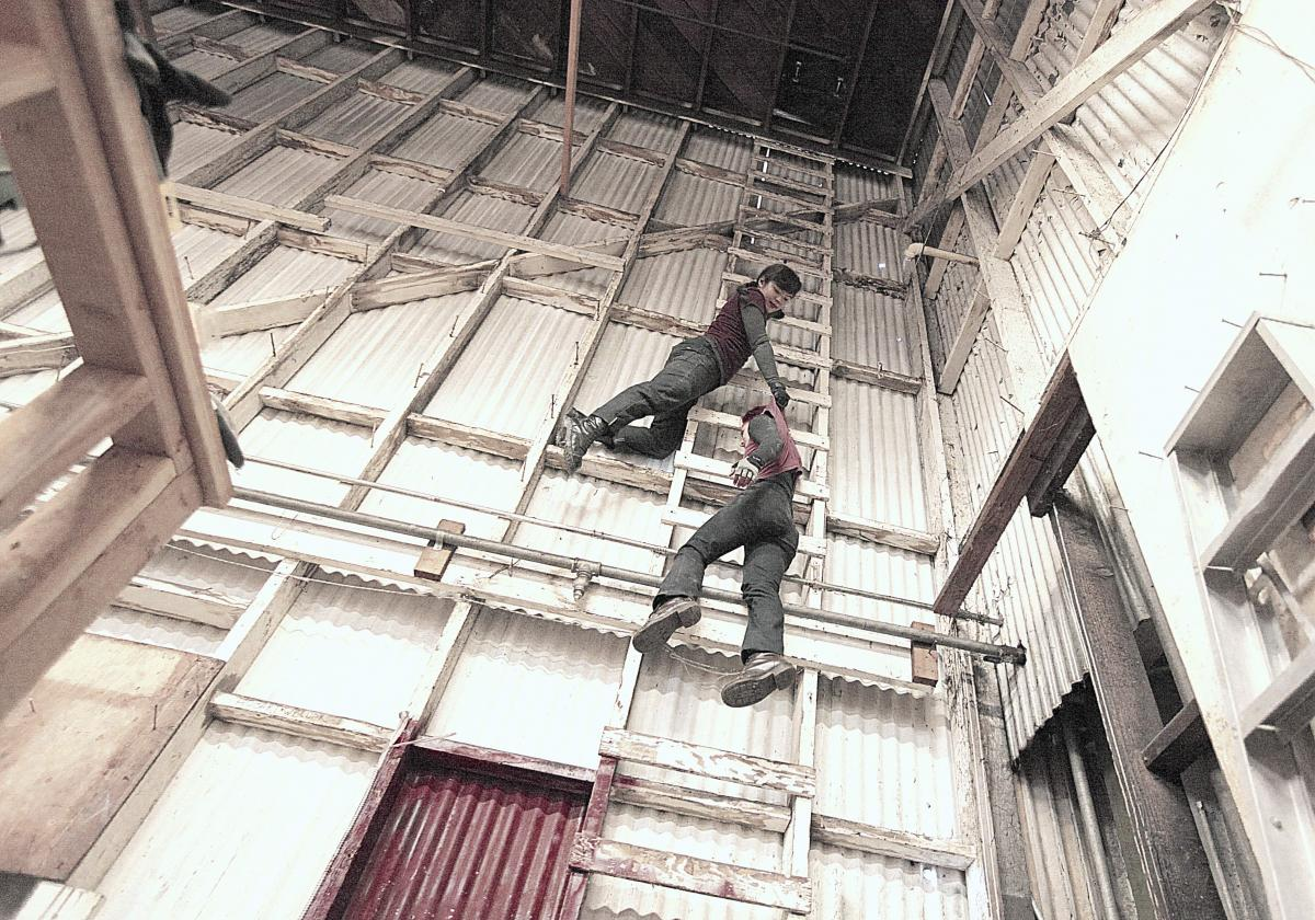 Megan Lowe and Sonsherée are high up on a white ladder in an industrial warehouse. Megan is holding onto the back of Sonsheree's shirt. Together they create an illusion that Sonsherée is dangling from the ladder and Megan is pulling her up by her shirt.
