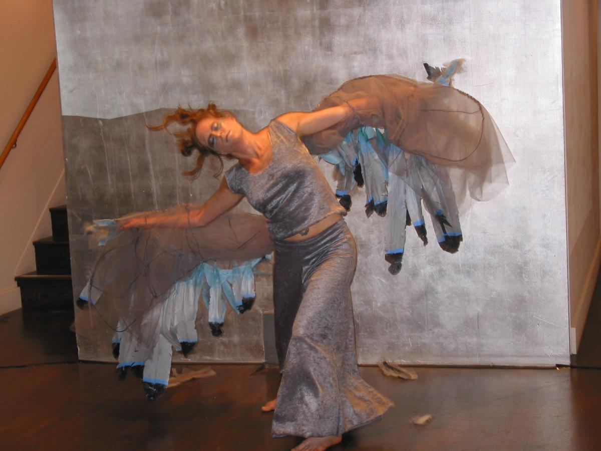 Dancer Amy Lewis, is wearing silver pants and a silver top. She has large feathered grey and silver wings strapped to her arms resembling a pigeon. She is in a deep lunge with her left leg forward and her head tipped to the right. Both wings are extended out parallel to the floor. She is caught in a moment between perching and taking flight.