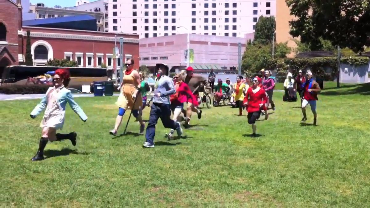 A group of people colorfully costumed are charging across a bright green field, all heading in the same direction.