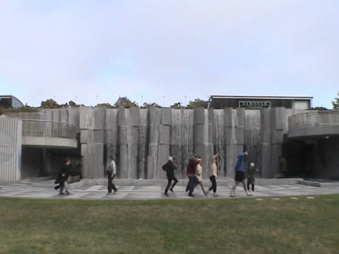 A handful of dancers traversing the concrete from left to right in front of the magnificent waterfall at Yerba Buena Gardens.